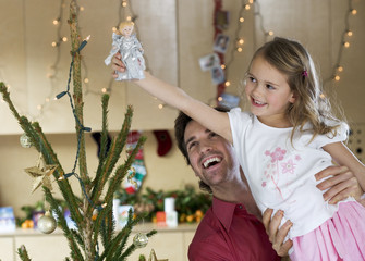 A father lifting his daughter to place the fairy on top of the Christmas tree