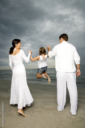 A couple with their daughter on a beach