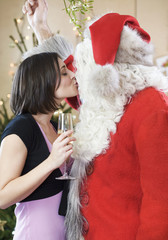 Santa Claus kissing a woman under the mistletoe
