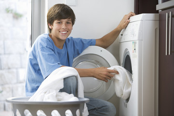 A young boy loading the washing machine