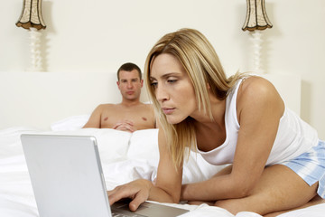 Young couple in bedroom, working on laptop