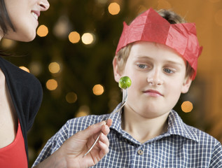A boy refusing to eat a Brussels sprout