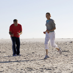 A mature couple exercising on a beach