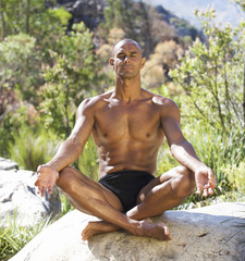 Young athletic man meditating