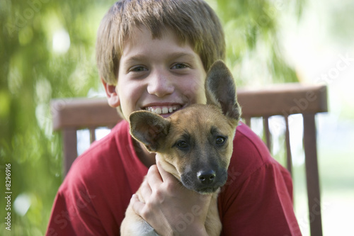 Young boy sitting in a garden chair holding a puppy