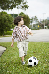 A young boy kicking football