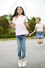 Two young girls skipping