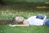 A teenage girl laying in a park