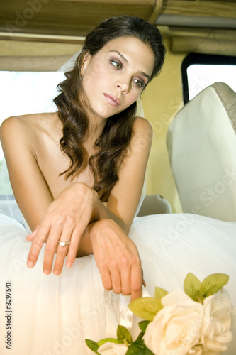 A bride sitting in the back of a car