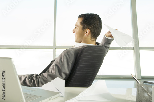 A businessman sitting at a desk making paper airplanes