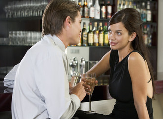 A couple drinking champagne in a bar
