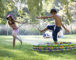 Young girl and boy playing in a paddling pool