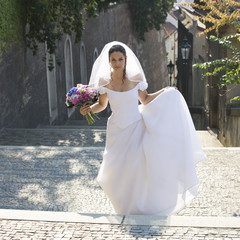 A bride walking in a cobbled street