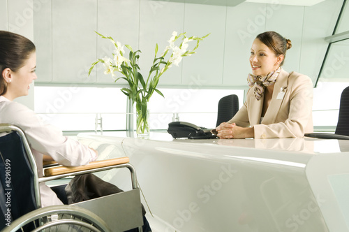 A receptionist greeting a woman in a wheelchair
