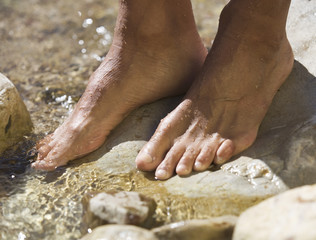 Close-up of feet in a stream