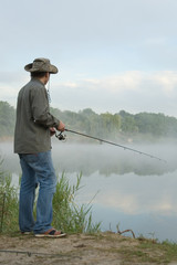 fisherman on a morning foggy lake