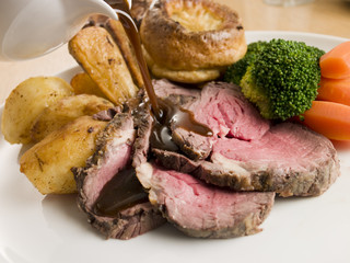 Gravy being Poured on a plate of Roast Beef