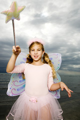 A young girl wearing a fairy costume