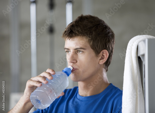 A young man drinking a bottle of water
