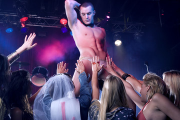 A hen party watching a male stripper