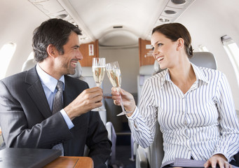 Two business colleagues drinking champagne on a flight