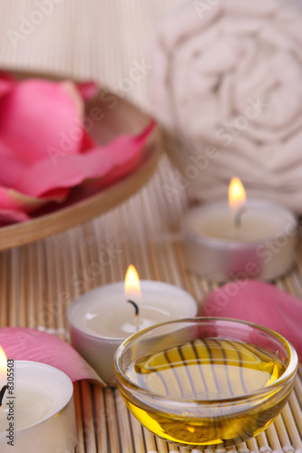 spa products with rose petals, oil container, towel and candles - 8305503