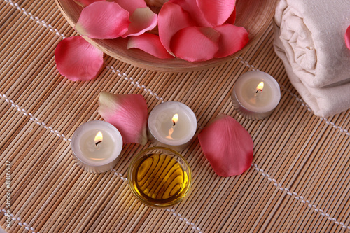 spa products with rose petals, oil container, towel and candles