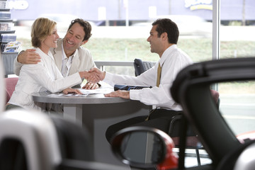 Couple sitting at desk in car showroom, salesman shaking hands with woman, smiling, side view