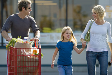 Family leaving supermarket, father pushing shopping trolley, mother and daughter (7-9) holding hands