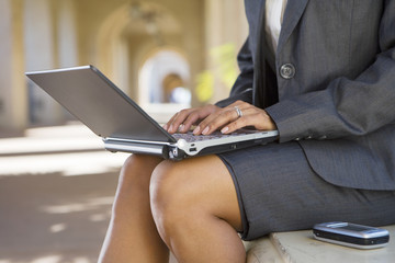 Businesswoman, in grey suit, using laptop in buiding arcade, side view, mid-section