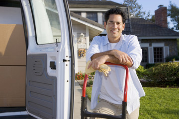 Man moving house, standing beside van in driveway, leaning on hand dolly, smiling, portrait