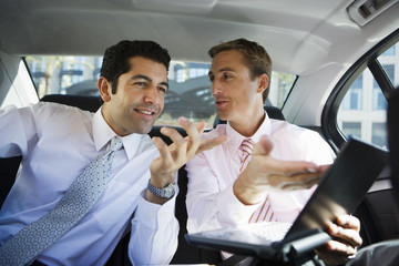 Two businessmen discussing work in back-seat of car, man gesturing to laptop screen, smiling
