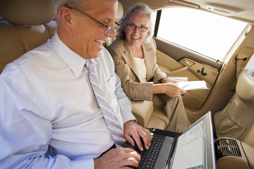 Businessman and woman sitting in back-seat of car, man using laptop, smiling, side view (tilt)