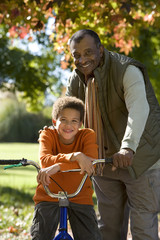 Father standing with son (7-9) in autumn park, boy sitting on bicycle, smiling, portrait