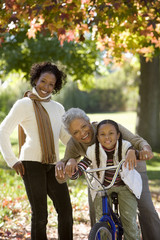 Girl (7-9) sitting on bicycle beside mother and grandmother in autumn park, senior woman embracing granddaughter, portrait