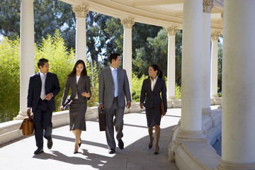 Four business colleagues walking side by side in colonnade, front view