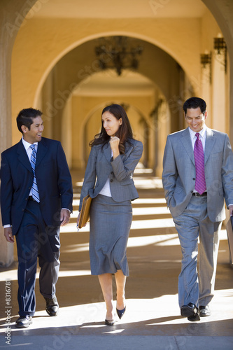 Businesswoman and two businessmen walking side by side in building arcade, laughing, front view