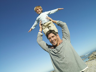 Boy (4-6) standing on father's shoulders at beach, arms out, smiling (tilt)