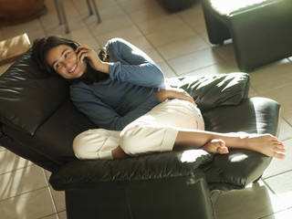 Teenage girl (17-19) reclining on leather armchair at home, using mobile phone, smiling, side view