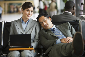 Two business people sitting in airport terminal, tired man resting head against woman's shoulder, woman using laptop