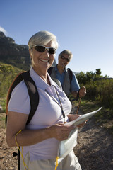 Mature couple hiking on mountain trail, woman standing in foreground, holding map, smiling, portrait