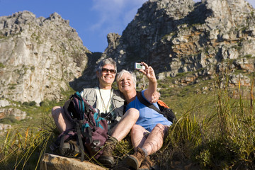 Mature couple sitting on mountain slope, woman taking self-portrait with digital camera, smiling, low angle view