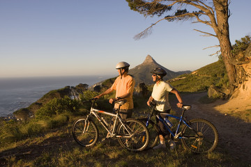 Mature couple standing with bicycles on mountain trail, looking at Atlantic Ocean horizon, side view