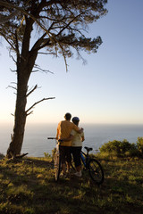 Mature couple standing with bicycles on mountain trail, looking at Atlantic Ocean horizon, rear view
