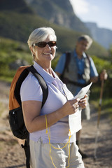 Mature couple, with rucksacks, hiking on mountain trail, focus on woman holding map and compass, smiling, portrait