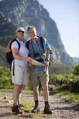 Mature couple, with rucksacks, hiking on mountain trail, woman holding map and compass, smiling
