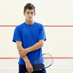 A young man with a squash racket