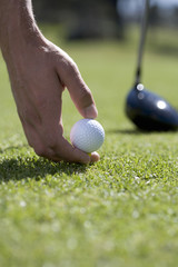 Man playing golf, close-up of hand, ball and tee