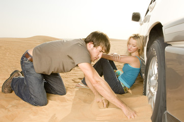 A couple couple digging their car out of the sand