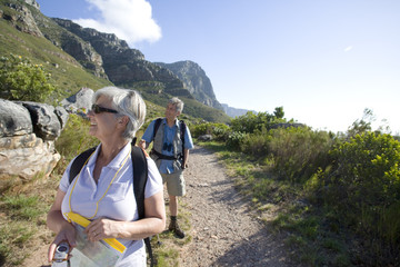 Mature couple, with rucksacks and hiking poles, hiking on mountain trail, woman leading, front view